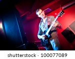 musician plays a guitar on a red background - stock photo