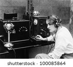 Woman sending Morse code using telegraph