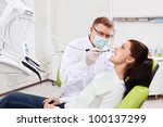 The dentist treats teeth of the patient in the clinic - stock photo