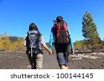 Hiking couple holding hands walking on volcano landscape on Teide, Tenerife, Canary Islands, Spain. - stock photo