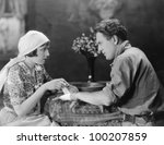 Woman bandaging mans hand - stock photo