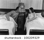 Couple in twin beds - stock photo