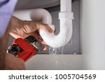 close up of male plumber fixing ... | Shutterstock . vector #1005704569