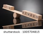 Small photo of Close-up Of A Wooden Seesaw Showing Imbalance Between Risk And Reward On Grey Background