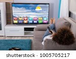 woman lying on sofa watching... | Shutterstock . vector #1005705217