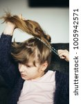 Small photo of Little girl making a ponytail at home