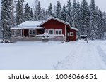 Red Wooden House In A Snowy An...