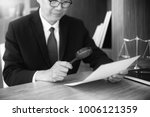 Small photo of Judge lawyer read paper text by use Magnify glass concept law firm Black and white color
