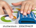 business woman uses a calculator | Shutterstock . vector #1006594639