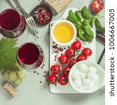 Small photo of Italian antipasti snack for wine. Mozzarella cheese, fresh basil leaves, tomatoes, olive oil and glasses of red wine on concrete background, top view. Caprese salat ingredients