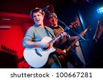 musician plays a guitar on a dark background - stock photo
