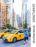 Small photo of New York City, USA - October 28, 2017: Midtown Manhattan with intersection of Columbus Circle and Broadway street road with many yellow taxi cab cars in traffic, woman running