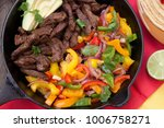 Small photo of Beef fajitas with bell pepper, onion, and avocado in cast iron skillet ready to be served.