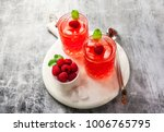 Small photo of alcoholic drink with raspberry liqueur and ice. two glasses of refreshing cocktail with berries and mint. alcoholic drink with raspberry liqueur and ice. on a stone background, copy space