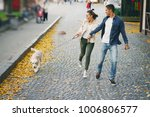 Stock photo brunette couple walking their golden retriever dog in the city on a sunny autumn day 1006806577