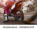 Small photo of Details of flying debris during an acceleration with mountain bikes race in dirt track in sunshine day time in blurry background. Concept of focus between an accelerate in action sport