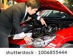 man writing note on engine... | Shutterstock . vector #1006855444