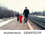 Small photo of The man is holding the baby by the handle, next to him is another girl. They walk along the platform along the railway. Winter