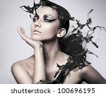 close up portrait of brunette woman with black splash - stock photo