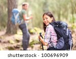 Hikers. Couple hiking in forest. Woman hiker smiling happy at camera walking with hiking poles. Young man in background. - stock photo
