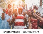 Small photo of Multinational football supporters celebrating the begin of world competition - Happy multiracial people having fun together outside of stadium - Main focus on black man - Sport and bonding concept