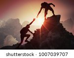 Help and assistance concept. Silhouettes of two people climbing on mountain and helping.