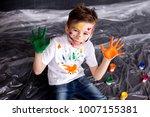 happy cute boy colors his hands.... | Shutterstock . vector #1007155381