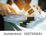 Small photo of Businesswoman hands working on Stacks of documents files for finance in office. Business report papers or Piles of unfinished document achieves with black clip paper. Concept of Business Annual Report