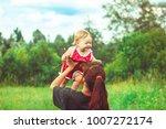 mom picks up daughter | Shutterstock . vector #1007272174