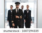 handsome pilot at airport with... | Shutterstock . vector #1007294335