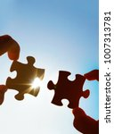 Small photo of two hands of businessman to connect couple puzzle piece with sky background.empty space.Jigsaw wooden puzzle against sun rays.two part of whole.symbol of association and connection.business strategy