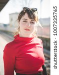 Small photo of portrait red dressed young beautiful woman posing outdoor looking camera smiling - positive emotions, happiness, carefree concept