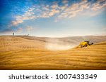 Small photo of Val D'Arbia, Tuscany June 15, 2017. Wheat harvest on the rolling Tuscan hills at sunset. Italy.