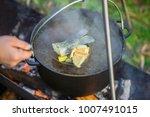Fish soup boils in cauldron at...