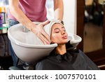 the hairdresser wraps the... | Shutterstock . vector #1007570101