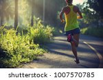 fitness young woman running on... | Shutterstock . vector #1007570785
