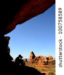Man wearing hat taking photographs of landscape in Arches - stock photo