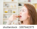 Small photo of young attractive asian woman who eats a serial bar