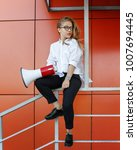 Small photo of A young attractive girl in a white shirt and glasses is holding a loudspeaker in her hands. Advertising campaign