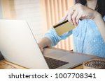 young woman holding credit card ... | Shutterstock . vector #1007708341