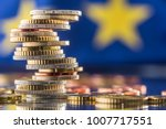 Tower with euro coins and flag of European Union in the background. - stock photo