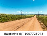 Small photo of Dirt road leading through green sugar cane plantations against blue sky in Eshowe, South Afruca