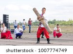 Small photo of Russia, Samara region, August 23, 2015: Russian Slavic fun, a man juggles with a log, showing his valiant daring