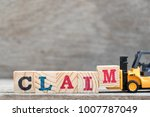 Small photo of Toy forklift hold letter block M to complete word claim on wood background