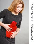 Small photo of Woman having strong stomach ache. Female suffer on belly pain, holding hot red water bottle on abdomen. Health care, remedy for pains concept