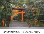 Stock photo a mother and child stand in front of a giant torii gate in a forest at the entrance to the usa 1007887099