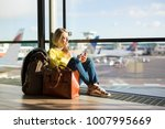 woman sitting in airport and... | Shutterstock . vector #1007995669