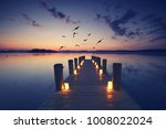 jetty with burning candles, romantic date, idyllic place - stock photo