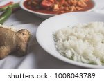 Small photo of a plate of white rice on the background of chicken paprika