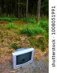 Small photo of Old analog television with a broken screen in forest